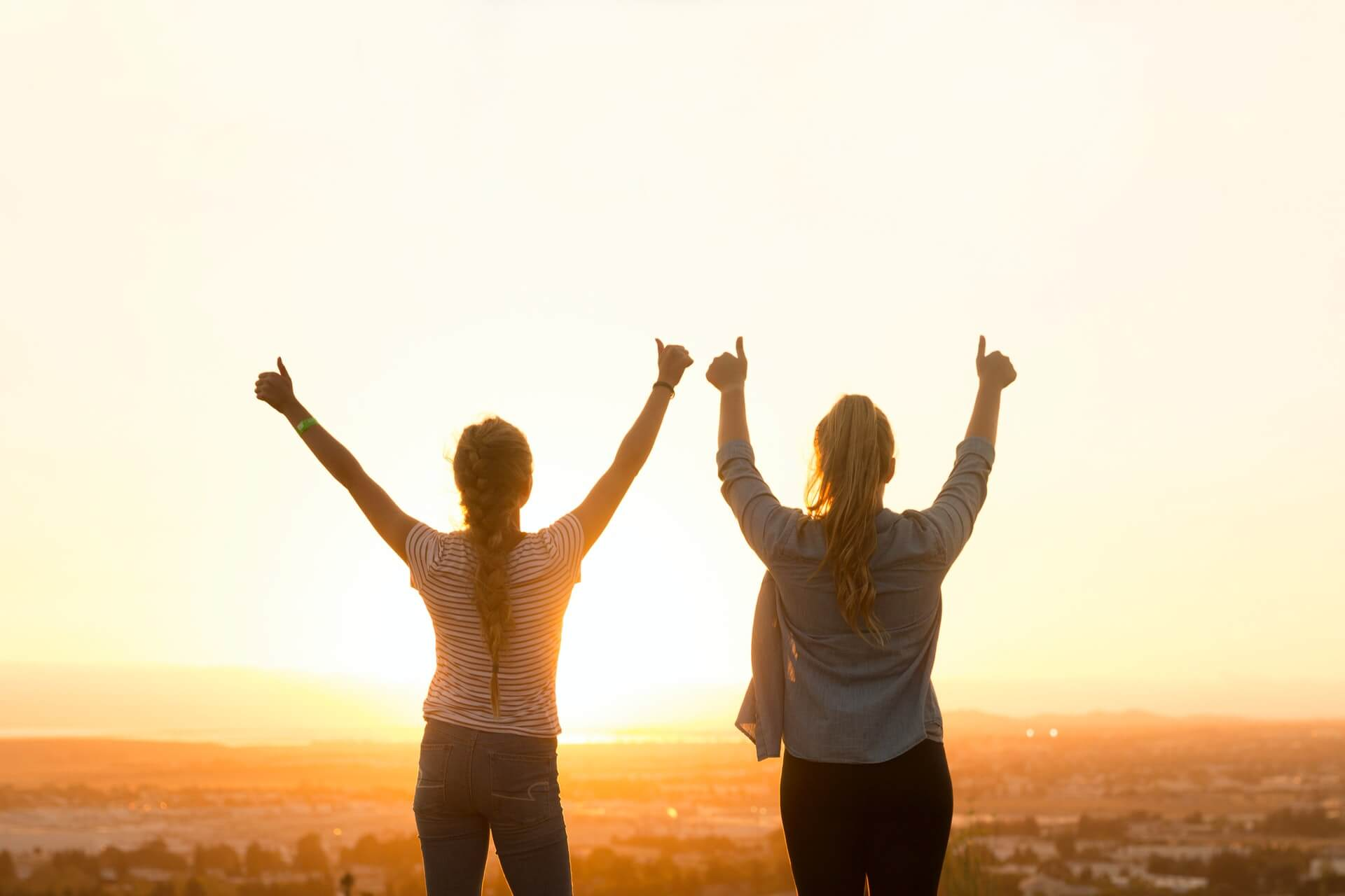 Two women hold their hands up in front of a sunset.