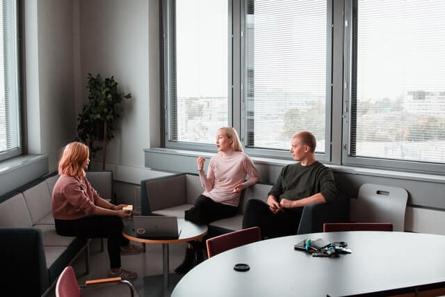 Three people sit together in a business meeting.