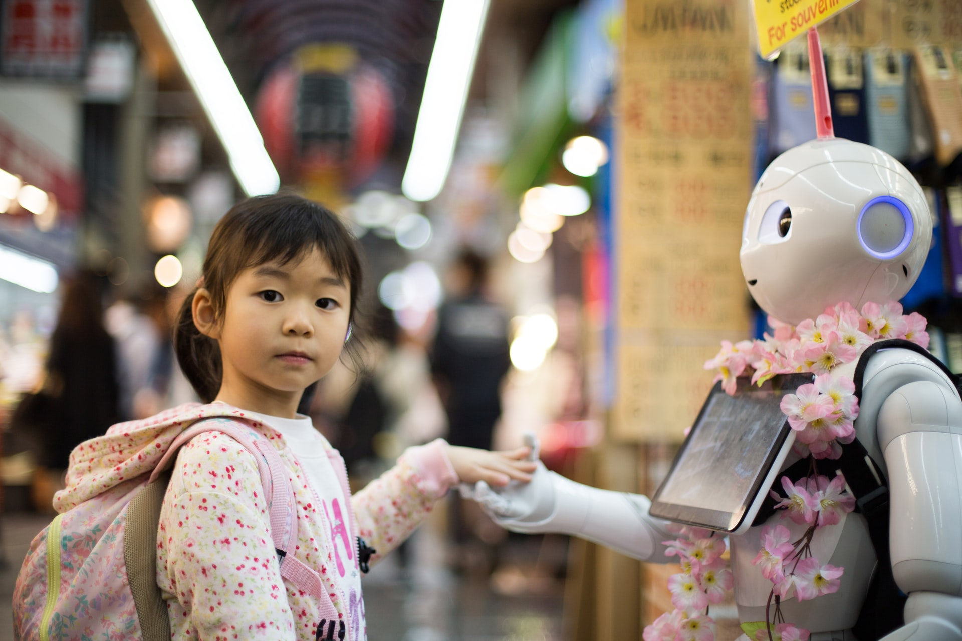 A girl interacts with a white robot.