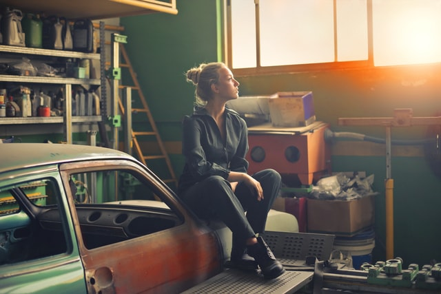 A woman sits on an orange car in a garage.