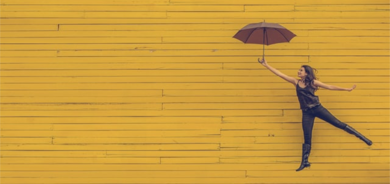 A woman holds a black umbrella near a yellow wall.