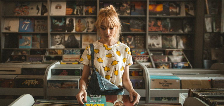 A blonde girl looks at a record in a shop.