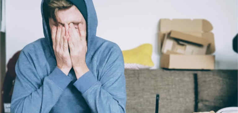 A man in a blue sweater covers his face with his hands.