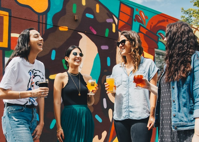 Four women laugh while holding drinks outside.