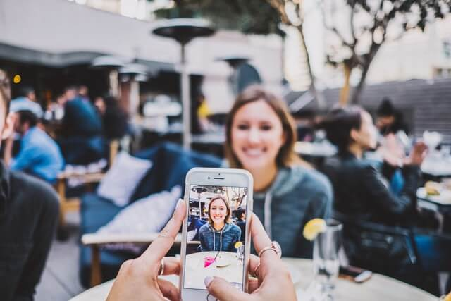 A girl has her photo taken with a smartphone.