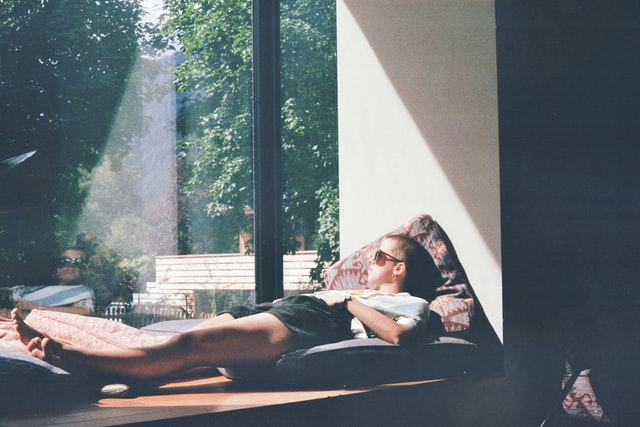 A man in a white t-shirt lies in the sunshine in a window seat.
