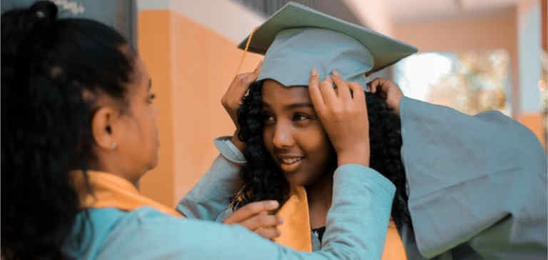A woman helps a young graduate girl put on her cap and gown.