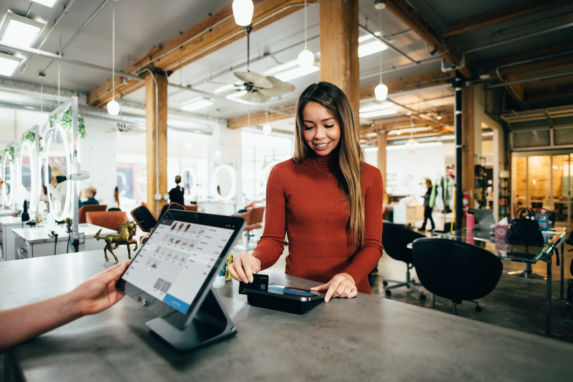 A woman in a red shirt uses her credit card at a cash register.