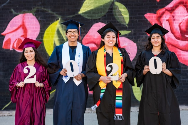 Four young graduates stand in front of a brick wall in their cap and gowns.