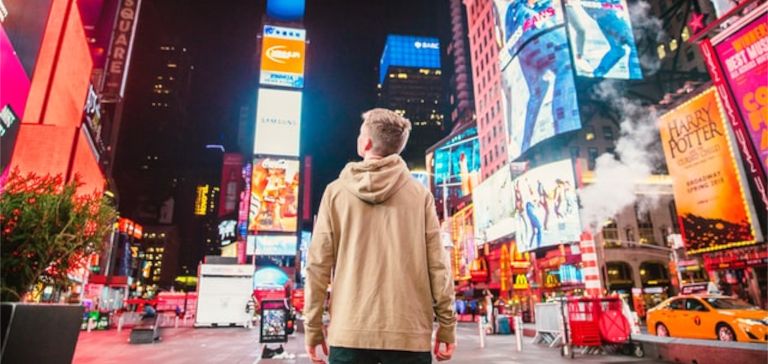 A man looks at advertisements in Times Square.
