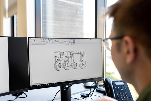 A man sits near a computer displaying a 3D rendering.