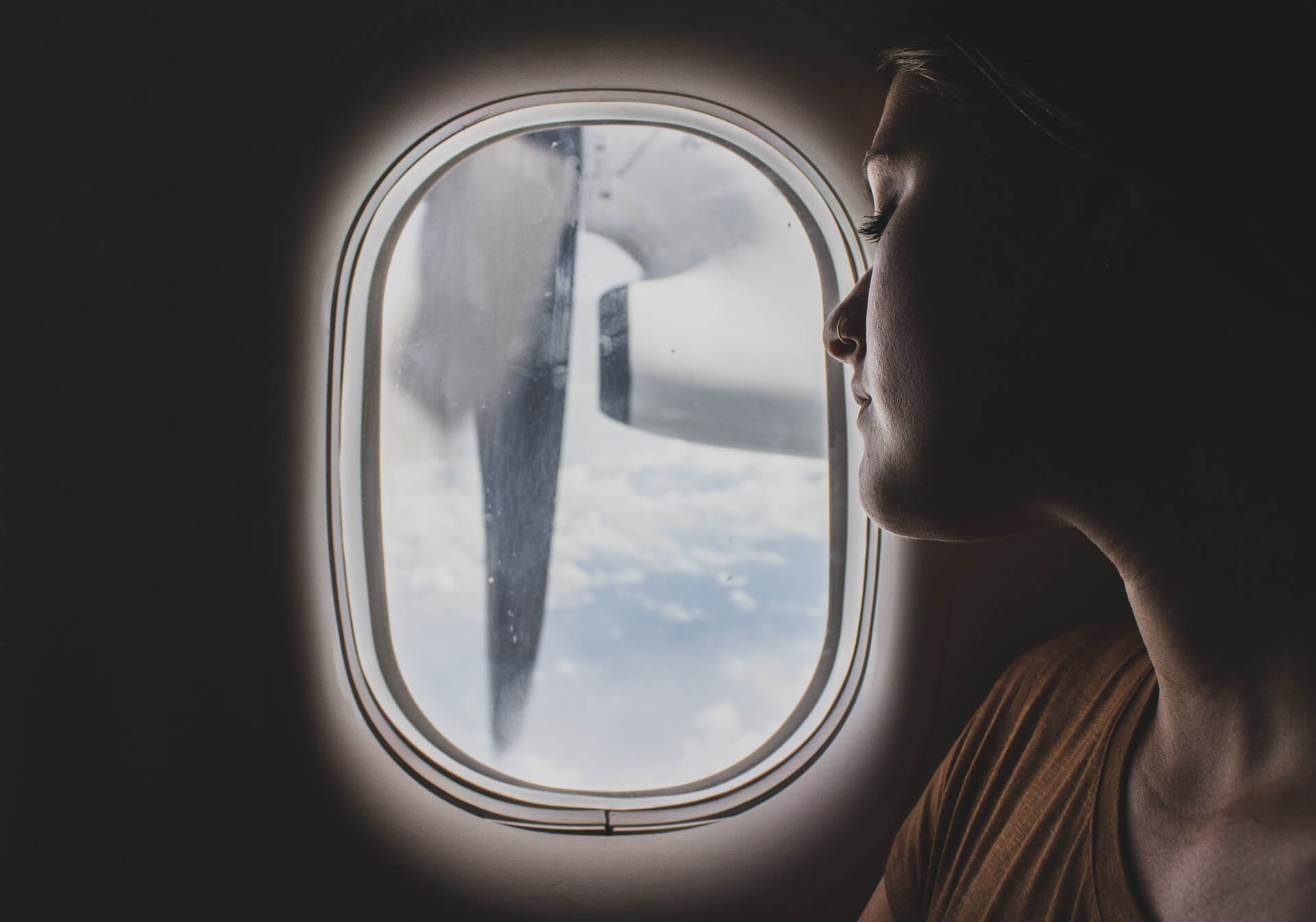 A woman looks out the window on an airplane.