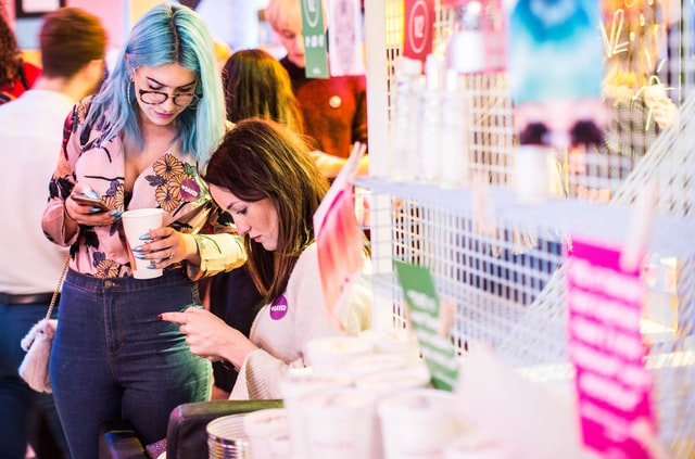 Two women on using smartphones in a shop.