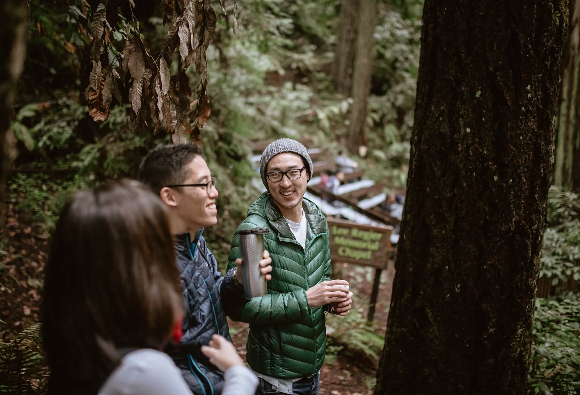 Three people in outdoor apparel laugh in a forest.