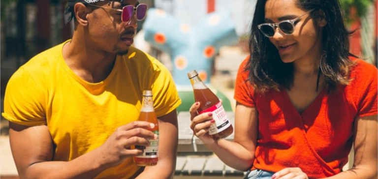 A man and woman sit in the sun with cold beverages.