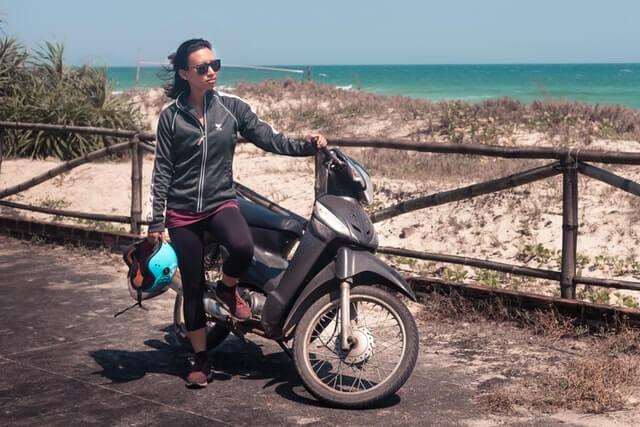 A woman stands near a motorbike holding a helmet.