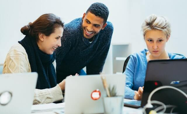 A man smiles while two women work on laptop computers.
