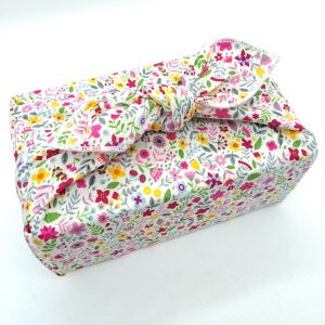 Gift wrapped with a cotton fabric furoshiki with pink wildflowers pattern