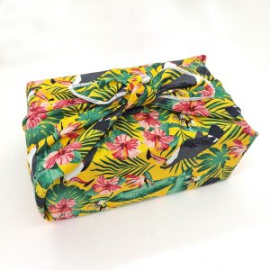 Gift wrapped in a furoshiki with yellow tropical toucan pattern