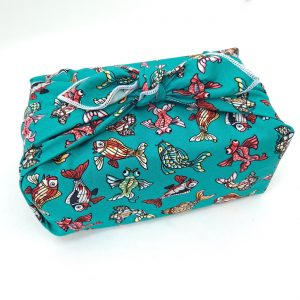 Gift wrapped in a furoshiki with a turquoise ornamental fish pattern