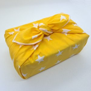 Gift wrapped in a yellow furoshiki with white stars
