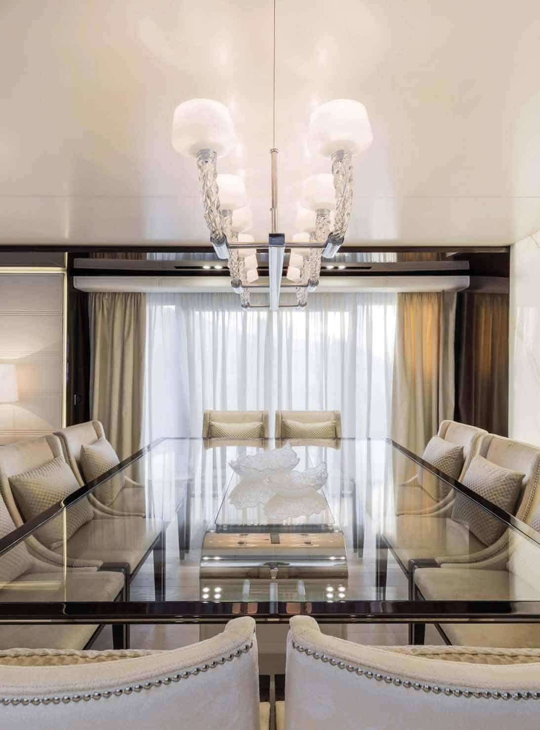 Il tavolo da pranzo in cristallo e l'elaborato lampadario in vetro di Murano