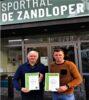 Schepen en directeur voor sporthal De Zandloper met energiecertificaten.