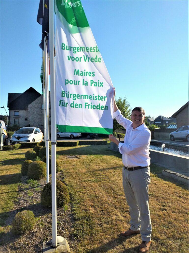Burgemeester Soetens met vlag voor gemeentehuis Lierde
