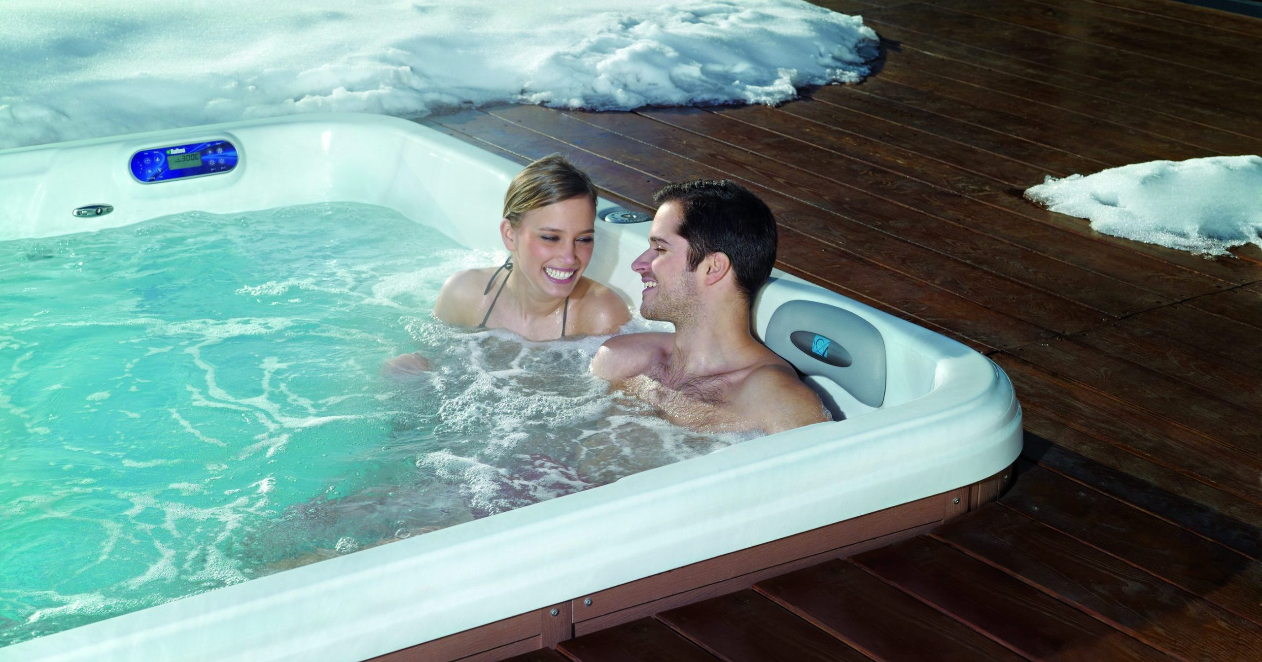 Man and woman enjoying a warm soak in a TidalFit swim spa