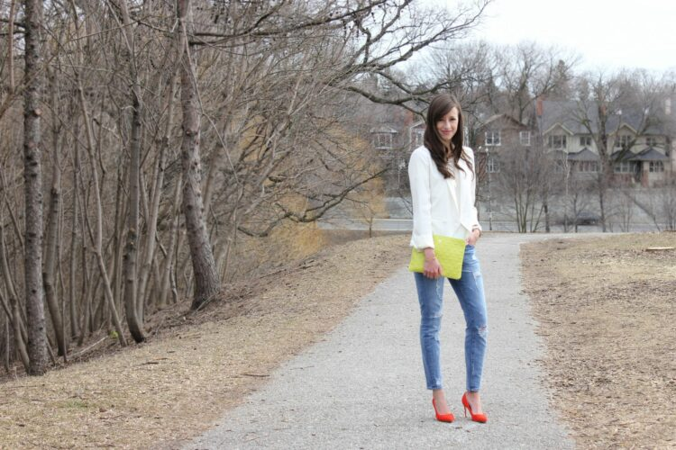 Girl in white top, jeans, red heels and a green bag.