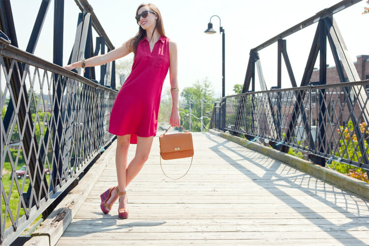Style Bee in a red tunic with Edie bag and woven platforms.