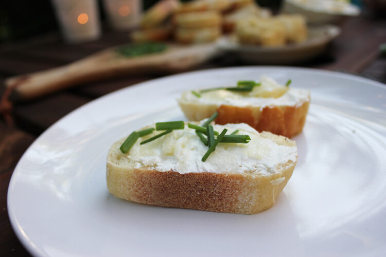 Roasted garlic with bread, cheese and chives.