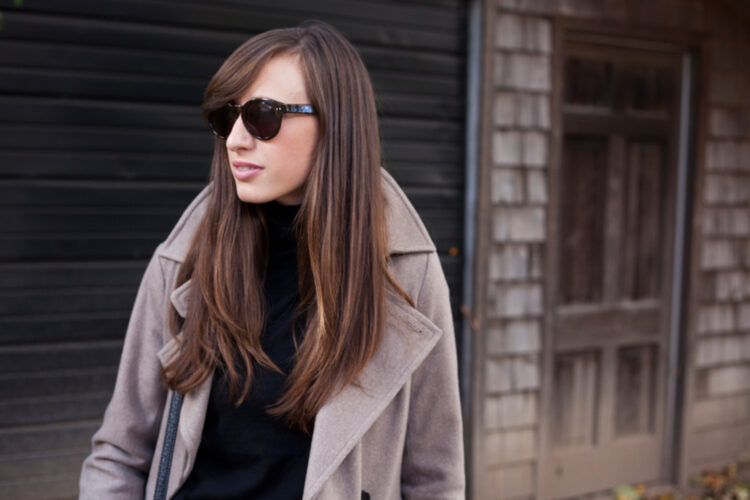 Style Bee in a black turtleneck, oatmeal trench and sunglasses.