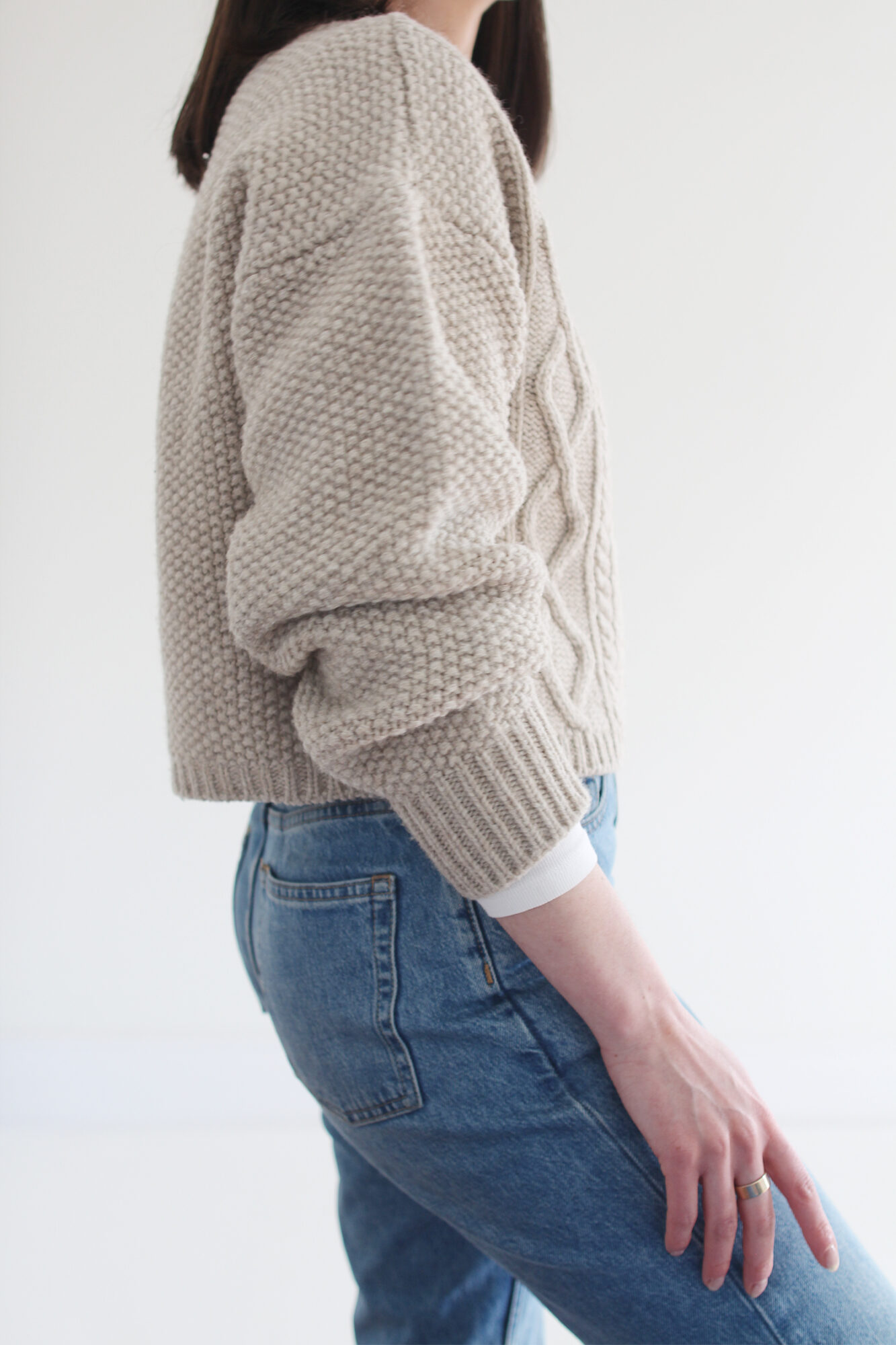 Woman wearing a beige cable knit sweater, vintage blue jeans, a tortoise headband and beige suede lug sole boots.