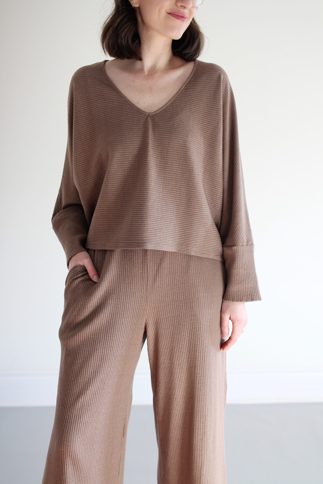 Woman wearing a cozy taupe cardigan over a matching minimalist lounge set in a taupe ribbed knit with fluffy slippers and clear framed glasses.