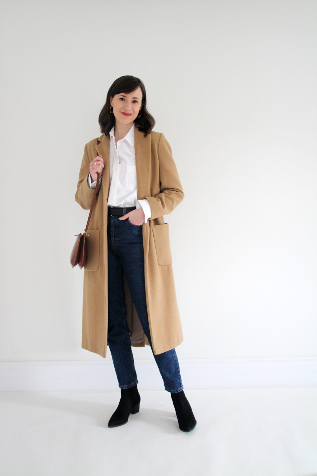 Woman wearing white button up, jeans, long camel coat, black boots, belt and brown leather bag.