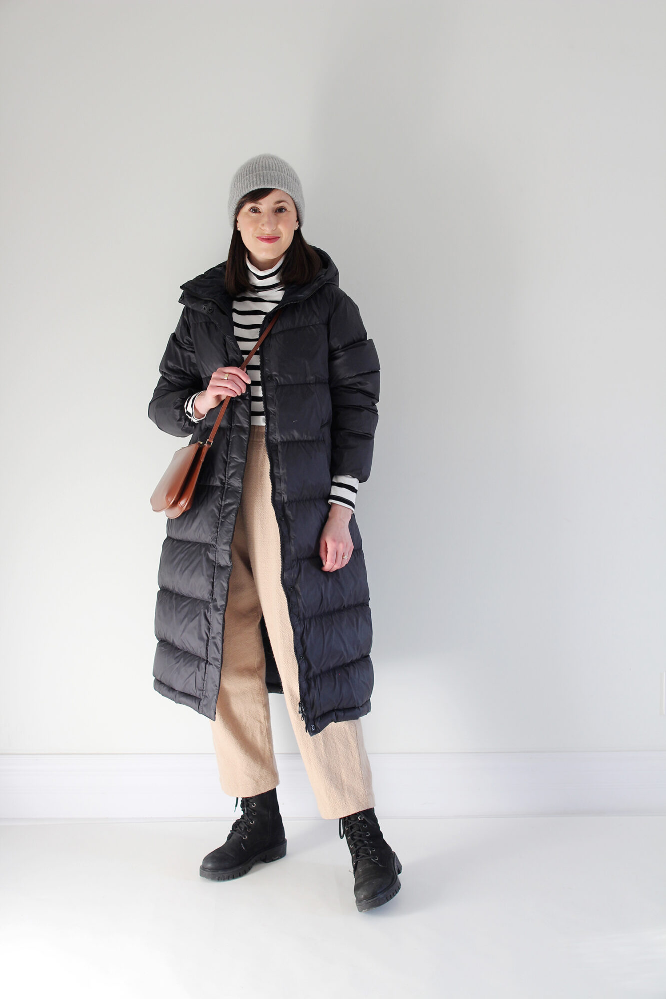 Woman wearing a long black puffer coat, striped turtleneck, tan wool trouser, black lace-up boot, grey beanie and brown leather bag.