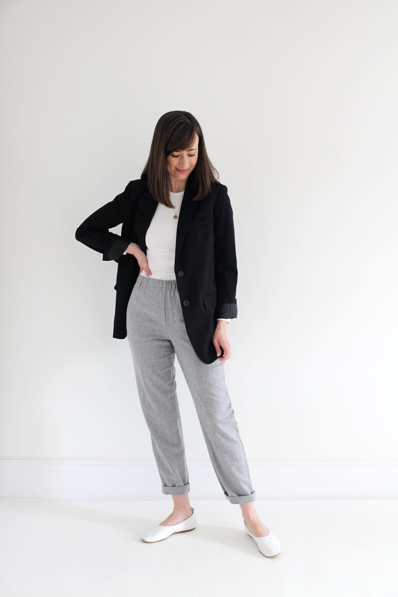 Woman wearing black blazer, white fitted t-shirt, grey joggers, white flats & a gold pendant necklace.