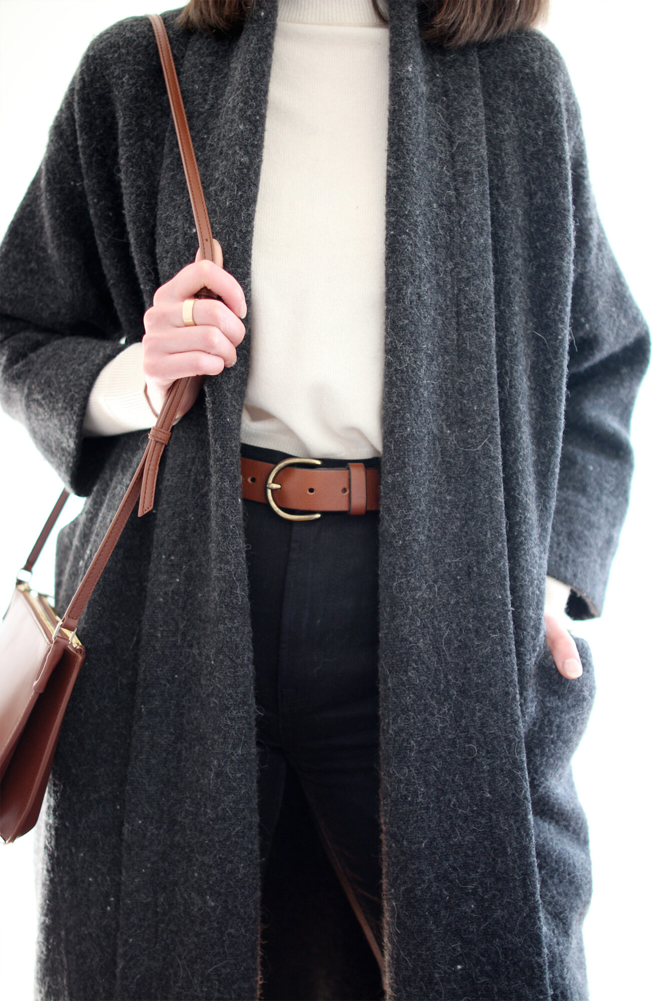 Woman wearing grey wool sweater coat, ivory mockneck sweater, brown leather belt, black jeans, black boots, and brown bag.