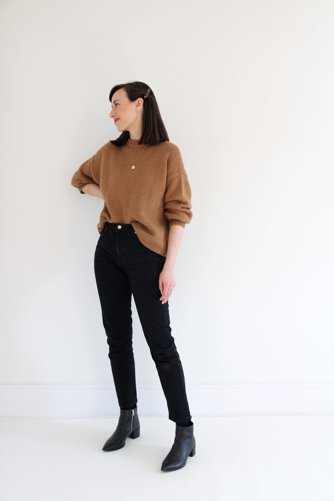 Woman wearing a relaxed alpaca knit sweater in camel, tucked into black jeans with gold jewelry and a tortoise barrette.