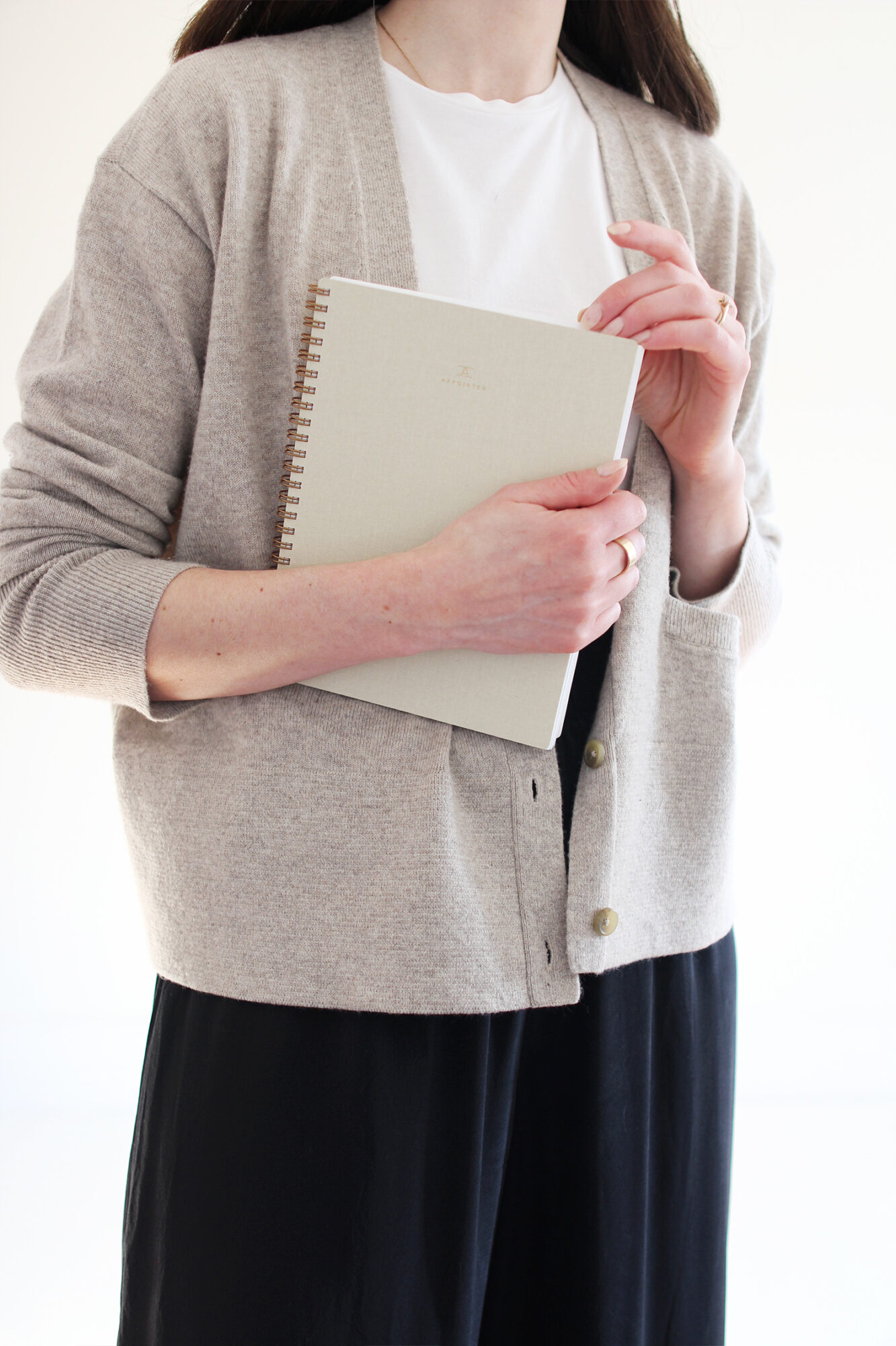 Style Bee wearing a white t-shirt, oatmeal cardigan, silk black pant, wheat knit flat, holding a lightweight notebook.