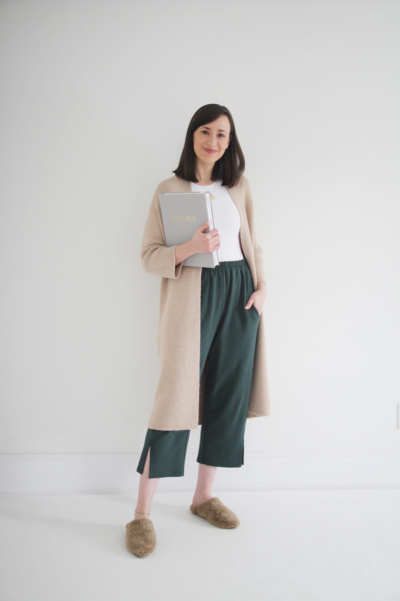Style Bee wearing a white  fitted top with cropped green lounge pants and a long camel cardigan with shearling slippers.