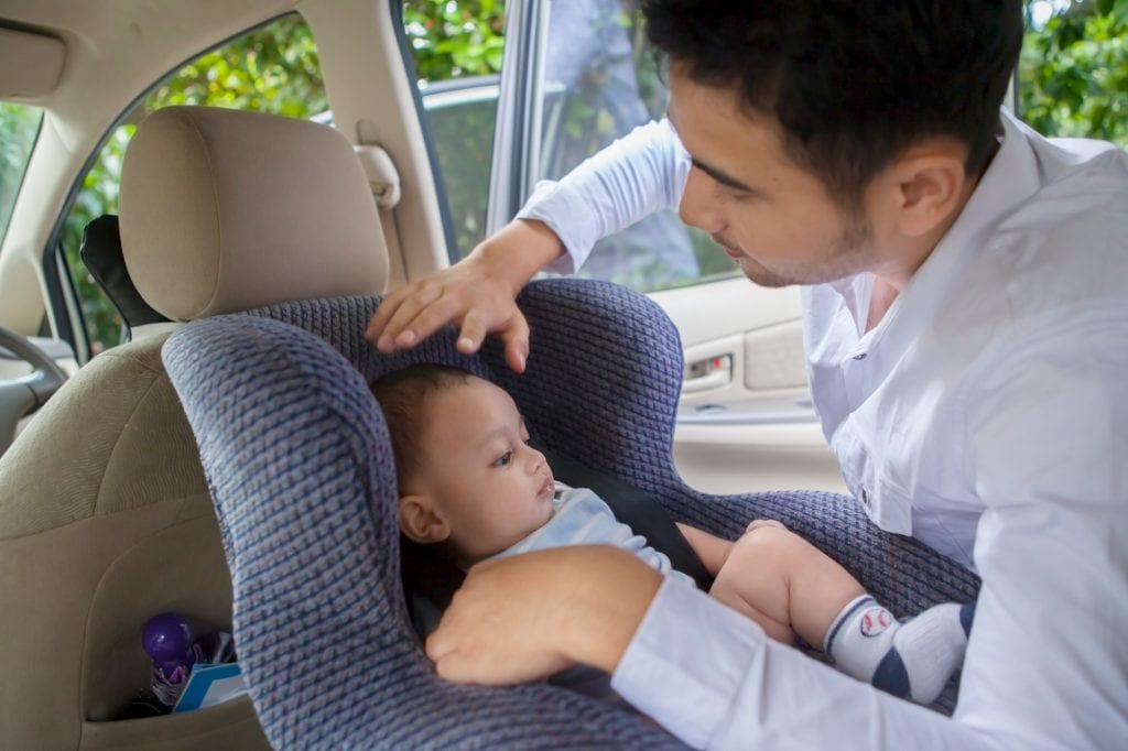 father-putting-child-in-carseat