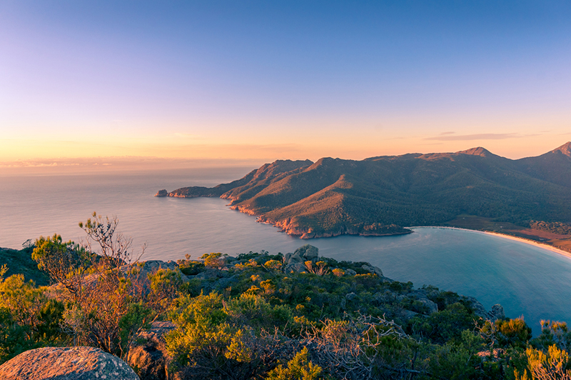 Sunrise landscape of ocean coastline with mountains and beach. Freycinet National Park in Tasmania, Australia