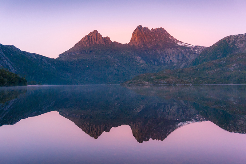 Cradle Mountain reflected in lake Dove at sunrise. Picturesque morning landscape with mountain peaks reflected in still water. Nature background