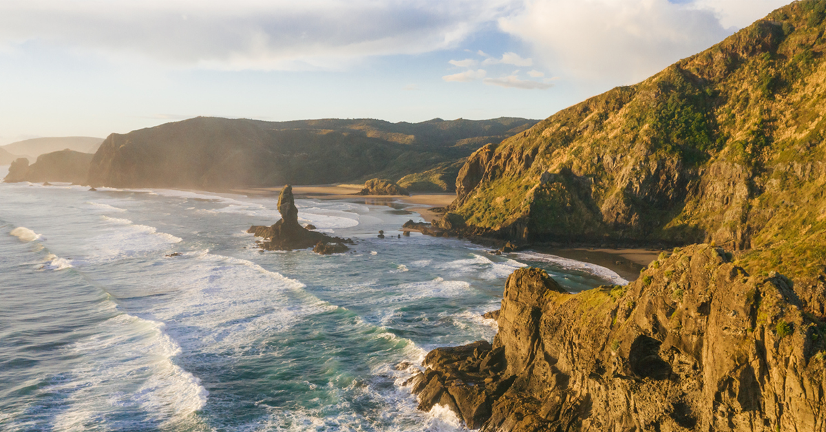 Rugged West Auckland coastline captured from above at sunset