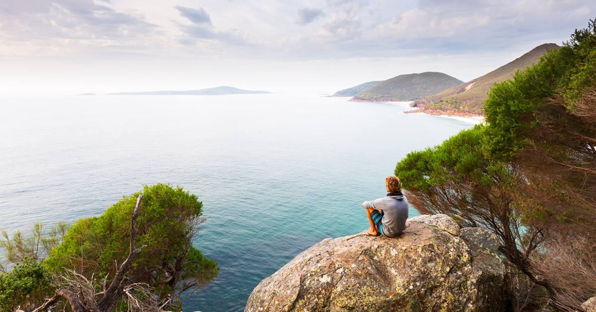 A man sits overlooking a panoramic view of a beautiful coastline near Newcastle, Australia.
