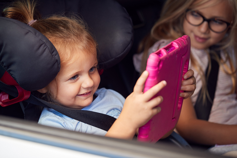 Two Young Girls Watching Digital Tablet In Back Seat On Car Journey