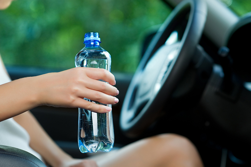 Young woman holding a bottle of water while sitting in the car close up