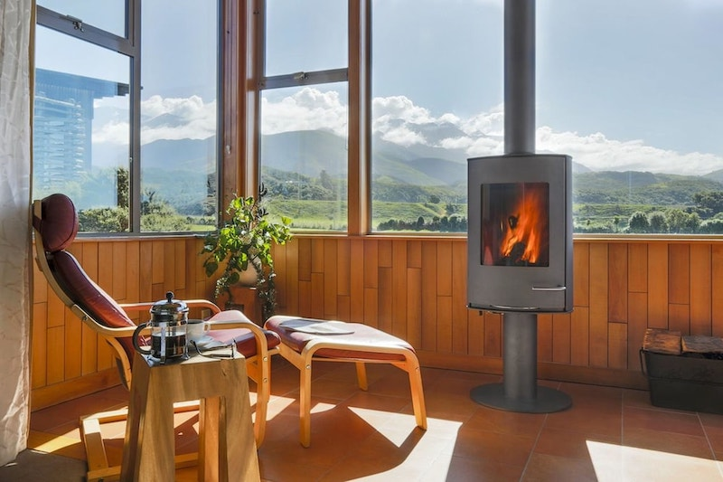 Fireplace and lounge chairs at hotel overlooking mountains